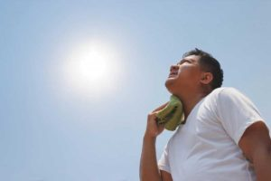 man-in-the-sun-holding-wet-cloth-to-neckW